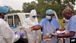 Health workers are handed personal protective gear by a team leader, right, before collecting the bodies of the deceased from streets in Monrovia, Liberia, Saturday, Aug. 16, 2014. New figures released by the World Health Organization showed that Liberia has recorded more Ebola deaths than any of the other affected countries. (AP Photo/Abbas Dulleh)