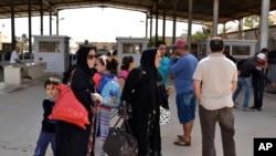 Perempuan Libya menyeberang ke Tunisia di perbatasan Ras Ajdir antara Libya dan Tunisia.