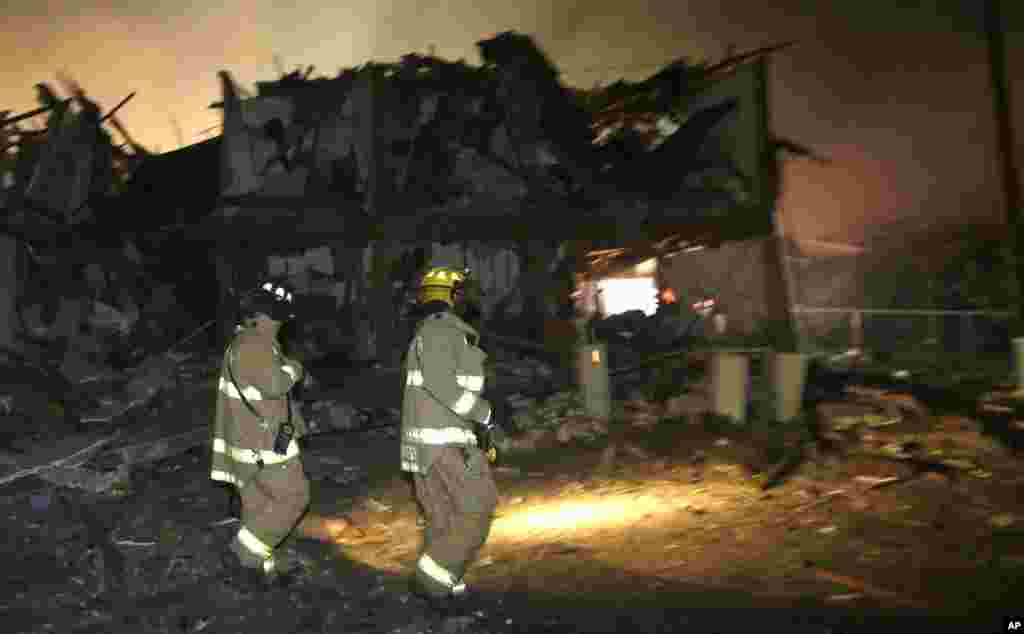 Firefighters walk next to a destroyed apartment complex near a fertilizer plant that exploded earlier in West, Texas, in this photo taken early morning April 18, 2013.
