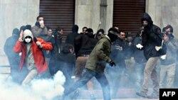 Протестувальники ховаються від сльозогінного газу під час сутичок із поліцією в центрі Афін