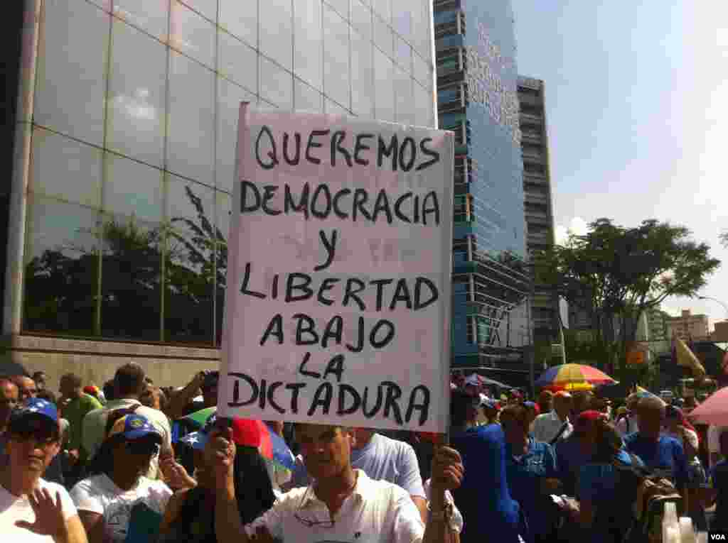 """Opposition supporters march in Caracas against President Nicolas Maduro, Oct. 26, 2016. Sign reads: """"We want democracy and freedom - down with dictatorship"""". (A. Algarra/VOA)"""