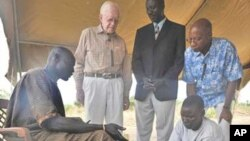 FILE - Former U.S. President and Carter Center Founder Jimmy Carter watches while Garbino, a young farmer with a Guinea worm disease, receives free treatment from a village volunteer trained by The Carter Center in partnership with the Government of Southern Sudan's Guinea Worm Eradication Program,Terekeka, Southern Sudan, Feb. 11, 2010.