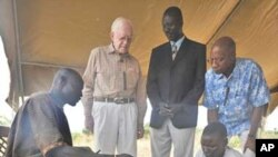 Feb. 11, 2010. Terekeka, Southern Sudan. Former U.S. President and Carter Center Founder Jimmy Carter watches while Garbino, a young farmer with a Guinea worm disease, receives free treatment from a village volunteer trained by The Carter Center in partne