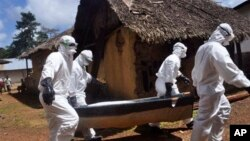 Petugas kesehatan membawa jenazah seorang perempuan yang diduga terkena virus Ebola di Bomi, luar kota Monrovia, Liberia (20/10). (AP/Abbas Dulleh)