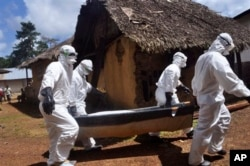 FILE - Health workers carry the body of a woman suspected of contracting the Ebola virus in Bomi county situated on the outskirts of Monrovia, Liberia, Oct. 20, 2014.