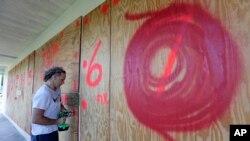 ساکنین فلوریدا، برای کاهش شدت توفان، بر درب و کلکین های منازل شان تخته ها را نصب کرده اند.