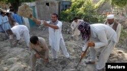 Nạn nhân động đất đứng trên đống đổ nát của một ngôi nhà tại Jalalabad, Afghanistan, ngày 24/4/2013.