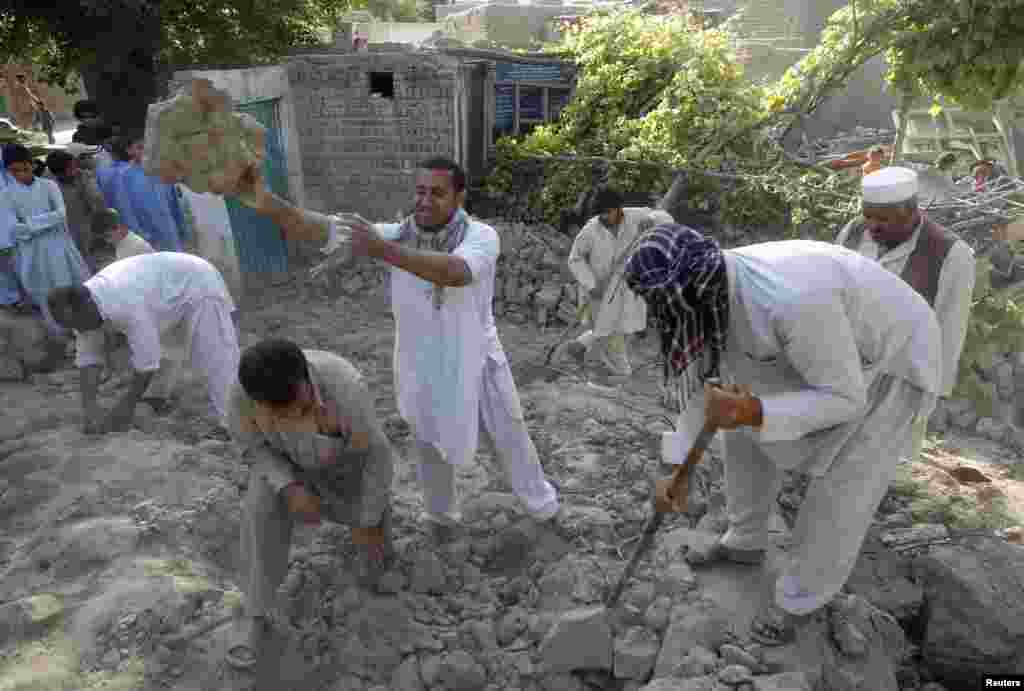 Earthquake survivors stand on the rubble of a mud house after it collapsed in Jalalabad province, Afghanistan, April 24, 2013.