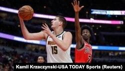 Nikola Jokić u duelu sa košarkašem Čikago Bulsa Džastinom Holidejom (Foto. Reuters/Kamil Krzaczynski-USA TODAY Sports)