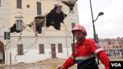 Seorang petugas penyelamat melewati gedung balaikota St. Agostino, wilayah Bologna yang rusak parah akibat gempa (20/5).