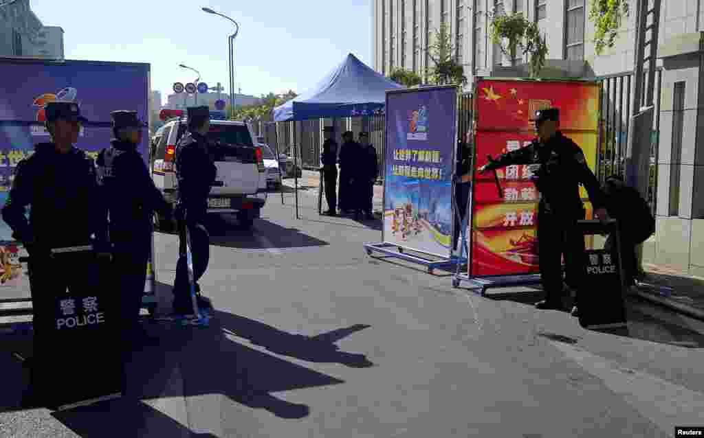 Police admit a vehicle through the checkpoint in Urumqi, Sept. 17, 2014.