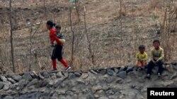 지난 4월 중국 단둥 접경 지역인 북한 신의주 압록강변에서 어린아이들이 둑에 앉아있다.