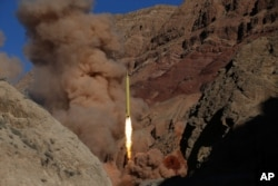In this photo from the Iranian Fars News Agency, a Qadr H long-range ballistic surface-to-surface missile is fired by Iran's powerful Revolutionary Guard, during a maneuver, in an undisclosed location in Iran, March 9, 2016.