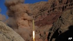 FILE - In this photo obtained from the Iranian Fars News Agency, a Qadr H long-range ballistic surface-to-surface missile is fired by Iran's powerful Revolutionary Guard, during a maneuver, in an undisclosed location in Iran.