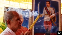 Cambodian man holds the burned incense sticks in front of a painted photo of a Kampuchea Krom Hero, Son Kuy, right, at a ceremony in Phnom, file photo.