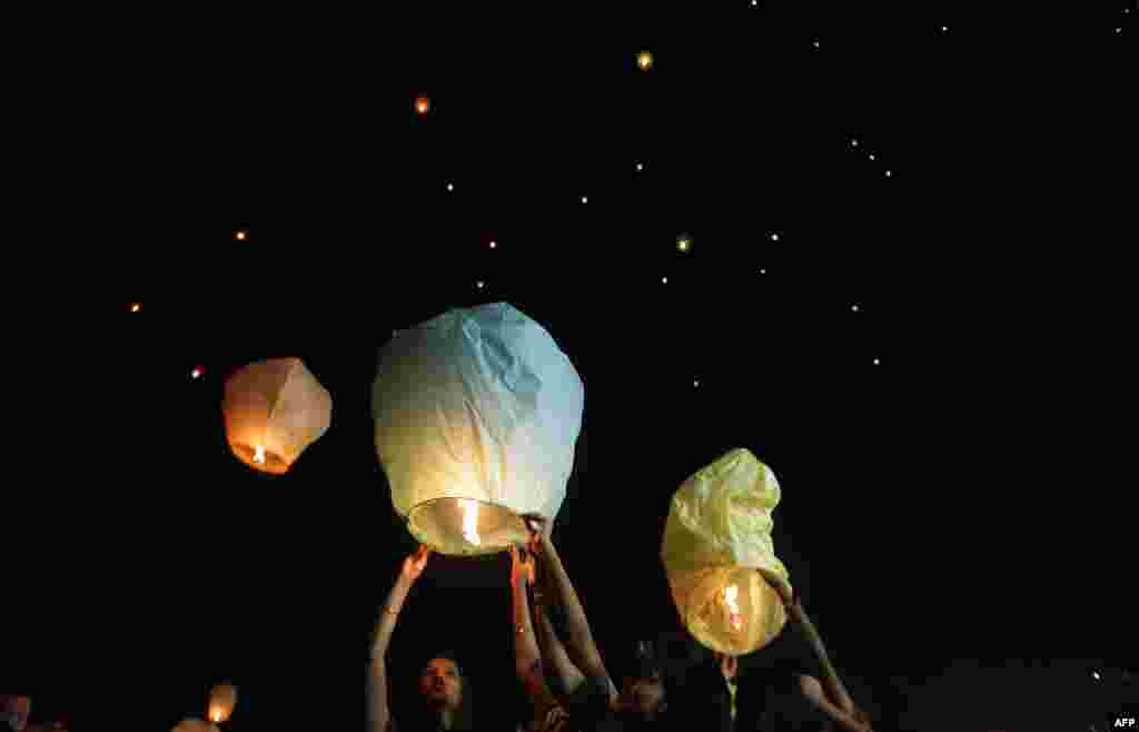 Indian volunteers of a social organization release lanterns in Kolkata to promote a peaceful and eco-friendly Diwali and create awareness against child labor in the fire cracker industry.