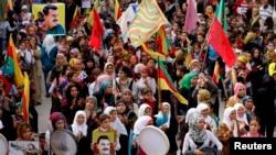 Para demonstran membawa foto-foto Abdullah Ocalan, pemimpin Partai Pekerja Kurdistan yang dipenjara dalam sebuah demonstrasi untuk mendukung pejuang Kurdi dan kota Suriah yang dikuasai ISIS, Kobani, di Aleppo, Suriah, 1 November 2014. (Foto: dok.)
