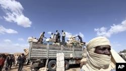 Immigrants, who are fleeing the unrest in Libya, unload their belongings in Agadez northen Niger September 15, 2011.