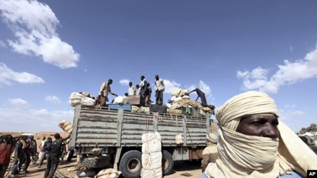 Immigrants, who are fleeing the unrest in Libya, unload their belongings in Agadez northen Niger September 15, 2011.