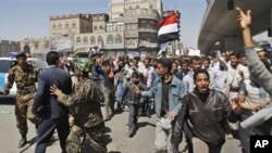 Yemeni police block the way as anti-government protestors attend a rally demanding political reform and the resignation of President Ali Abdullah Saleh in Sanaa, Yemen, February 13, 2011