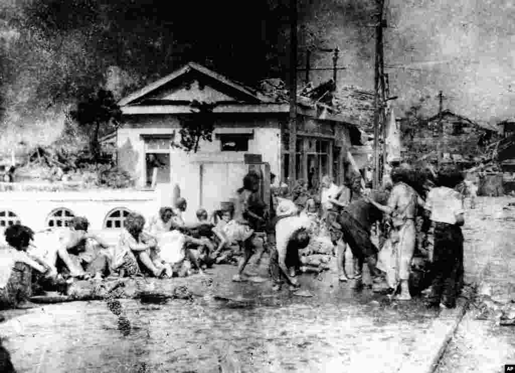 "Japanese victims wait to receive first aid in the southern part of Hiroshima, Japan, a few hours after the U.S. atomic bomb exploded in the heart of the city on Aug. 6, 1945. The explosion of the first A-bomb, known as ""Little Boy,"" instantly killed 66,00"
