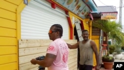 Men board up buildings ahead of Hurricane Maria in Sainte-Anne on the French Caribbean island of Guadeloupe, Monday, Sept. 18, 2017.