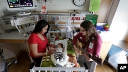 Music therapist Elizabeth Klinger, right, quietly plays guitar and sings for a baby as he grips the hand of his mother in the newborn intensive care unit at Ann & Robert H. Lurie Children's Hospital in Chicago, May 6, 2013.