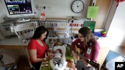 Music therapist Elizabeth Klinger, right, quietly plays guitar and sings for a baby in the newborn intensive care unit at Children's Hospital in Chicago, May 6, 2013.