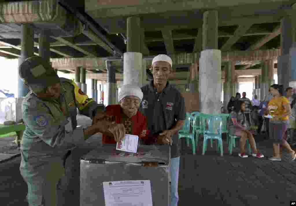 کمک کردن کارمندان حوزه رای گیری به زنی مسن برای انداختش رای اش به درون صندوق در انتخابات اندونزی