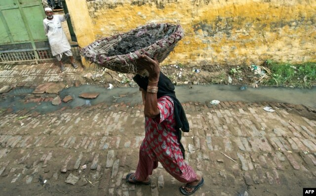 FILE - 60 year old manual scavenger Kela carrying a basket of human excrement her head after cleaning toilets in Nekpur village, Muradnagar in Uttar Pradesh, some 40 kms east of New Delhi, August 10, 2012.