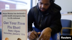 Oddelio Reid fills out paperwork before getting an influenza vaccine injection during a flu shot clinic at Dorchester House, a health care clinic, in Boston, Massachusetts January 12, 2013.