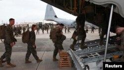 FILE - Marines board a KC-130J Hercules aircraft at the U.S. Futenma airbase on the Japanese island of Okinawa.