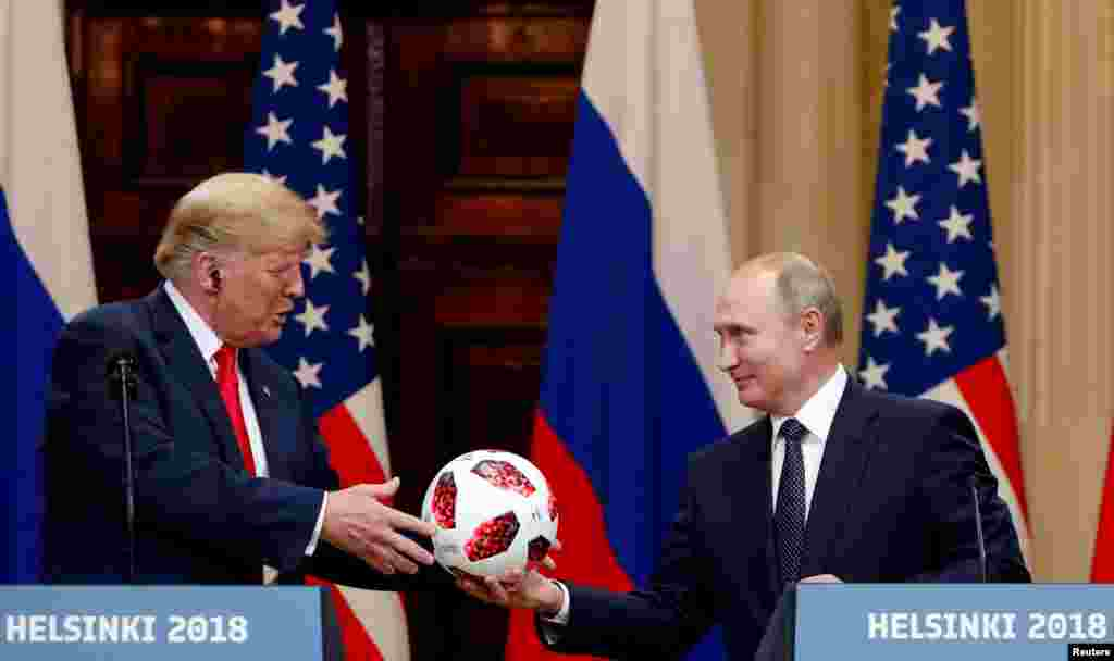 U.S. President Donald Trump receives a football from Russian President Vladimir Putin during their joint news conference after their meeting in Helsinki, Finland.