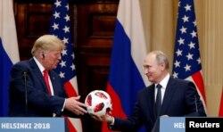 El presidente de EE. UU., Donald Trump, recibe una pelota de fútbol del presidente ruso, Vladimir Putin, mientras celebran una conferencia de prensa conjunta después de su reunión en Helsinki, Finlandia el 16 de julio de 2018. REUTERS / Grigory Dukor.