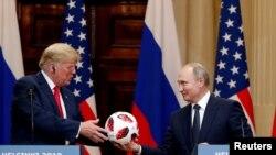 روسی صدر پوٹن پریس کانفرنس کے دوران ورلڈ کپ کا فٹ بال صدر ٹرمپ کو پیش کر رہے ہیں۔