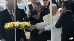 Le pape François, debout sur un bateau de la Garde côtière, jette une couronne de fleurs dans la mer en mémoire des migrants qui n'ont jamais atteint leur destination, lors de sa visite à l'île de Lampedusa, au sud de l'Italie, 8 juillet 2013.