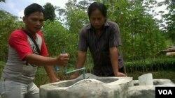 Pak Suharyanto (kiri), peternak kambing di Kabupaten Sleman, Yogyakarta, memeriksa reaktor biogas yang sekaligus dijadikan sarana pengolahan pupuk organik (foto: VOA/Nurhadi).