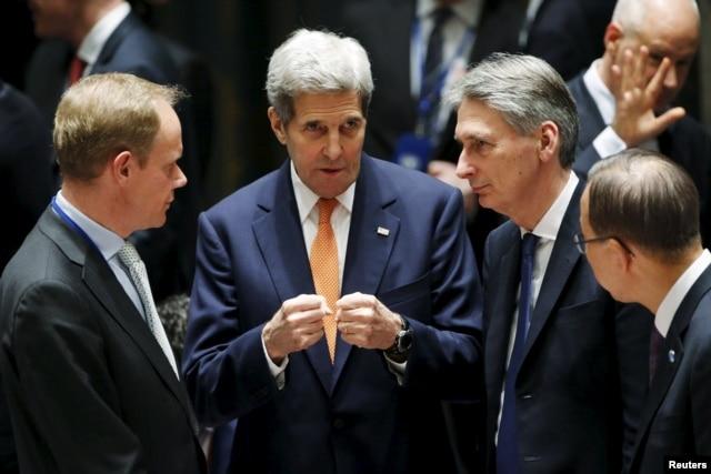 FILE - From left, British Ambassador to the U.N. Matthew Rycroft, U.S. Secretary of State John Kerry, Britain's Foreign Secretary Philip Hammond, U.N. Secretary General Ban Ki-moon speak before a meeting of the U.N. Security Council in New York, Dec. 18, 2015.