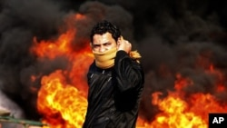 A protester stands in front of a burning barricade during a demonstration in Cairo, Jan 28, 2011