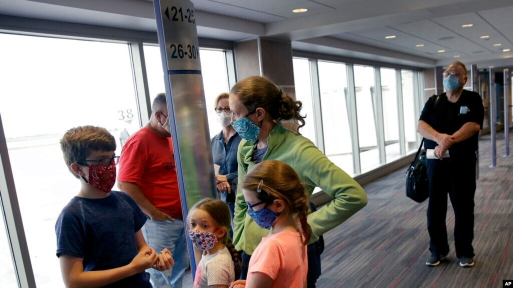 FILE - People wearing masks wait to board a flight in Kansas City, Mo., May 24, 2020. Governments and businesses are scrambling to change course following new federal guidance calling for the return of mask wearing in virus hot spots.