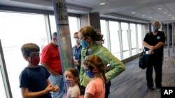 FILE - People wearing masks wait to board a flight in Kansas City, Missouri, May 24, 2020. Governments and businesses are scrambling to change course following new federal guidance calling for the return of mask wearing in virus hot spots.