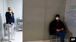 "Seorang perawat berdiri di dalam bilik pusat vaksinasi COVID-19 ""Promitheas Center"", di Athena, Yunani, saat seorang pria menunggu untuk disuntik vaksin Moderna, Senin, 15 Februari 2021."