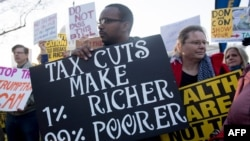 FILE - Demonstrators against a Republican tax reform bill hold a 'People's Filibuster to Stop Tax Cuts for Billionaires' protest rally outside the US Capitol in Washington, Nov. 30, 2017.