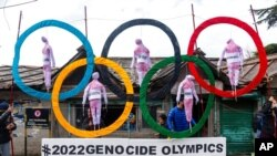 FILE - Exile Tibetans use the Olympic rings as a prop as they protest the holding of the 2022 Winter Olympics in Beijing, in Dharmsala, India, Feb. 3, 2021.