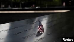 Una bandera estadounidense es colocada en uno de los nombres en la fuente reflectante en el Monumento conmemorativo del 11 de Septiembre en la ciudad de Nueva York.