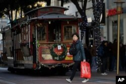 A woman carries a shopping bag while walking in front of a cable car in San Francisco, Nov. 29, 2019.