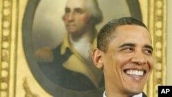 ປະທານາທິບໍດີບາຣັກ ໂອບາມາ ຢືນຍິ້ມຢູ່ຕໍ່ໜ້າຮູບ ທ່ານ George Washington ປະທານາທິບໍດີຄົນທໍາອິດ ຂອງສະຫະລັດ ທີ່ຫ້ອງການ ຮູບໄຂ່ ຫລື Oval Officeຂອງທໍານຽບຂາວ.