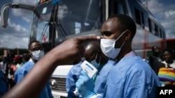 Un membre du Centre biomédical du Rwanda prend la température des passagers à un gare routière à Kigali, le 22 mars 2020 ( AFP / Simon Wohlfahrt )