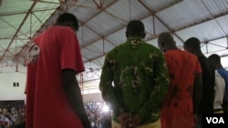 Six young men accused in an attack that injured Red Cross workers in Forecariah, Guinea, apologize at a public meeting before their release Sept. 26, 2014. (Carol Guensburg/VOA)