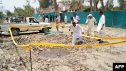 Pakistani security officials examine a crater caused by overnight suicide bombing in the southern city of Sukkur. on July 25, 2013.